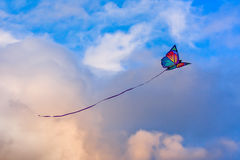 Living in the clouds. Butterfly shaped kite in the blue sky Stock Images