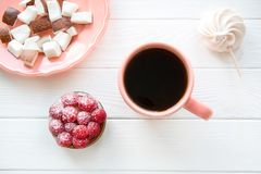 Living coral color cup and plate on white table. Background. Coconut pieces and raspberry tart and merengue, top view royalty free stock photography