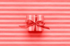 Living Coral color of the Year 2019 Gift box with bow on striped. Wrapping paper. Abstract geometric background stock photography