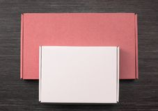 Living coral and white colors carton boxes on dark wooden desk. Copy space. Top view.  royalty free stock photos