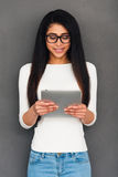 Living in digital age. Attractive young African woman holding digital tablet and looking at it while standing against grey background stock image