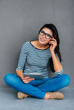 Living in digital age. Attractive young woman holding digital tablet and looking at camera with smile while sitting on the floor and against grey background stock photo