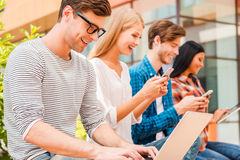 Living in digital age. Group of young people holding different digital devices and smiling while sitting in a row outdoors royalty free stock images