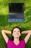 Living in digital age. Top view of beautiful young woman lying in grass and smiling while while laptop laying upon her head stock photos