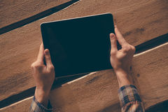 Living in digital age. Top view close-up image of man holding digital tablet while sitting at the rough wooden table stock images