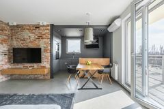 Contemporary industrial styled flat. Living and dining space in contemporary styled flat with big windows royalty free stock photo