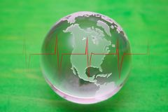 Living Earth with heartbeat. Crystal ball globe on a green painted background with a red heartbeat trace Royalty Free Stock Images