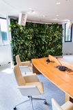 Living green wall, vertical garden indoors with flowers and plants under artificial lighting in meeting boardroom stock image