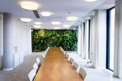 Living green wall, vertical garden indoors with flowers and plants under artificial lighting in meeting boardroom royalty free stock photo