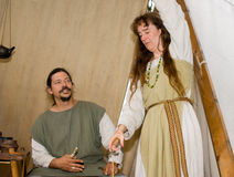 Living in mediaeval. Farmer and his wife in middle ages during a camp. she is making yarn by hand Stock Photo