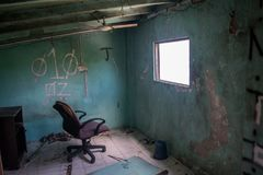 Living room with chair in front of window in the ruined abandoned burned house Royalty Free Stock Image