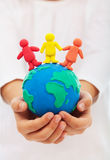 Living in peace and understanding concept. Living in peace and understanding - concept with clay earth and different colored people Stock Photography