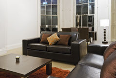 Living room. Detail of a living room with massive bay window and modern furniture Royalty Free Stock Photography