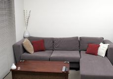 Living Room. Corner Of A Living Room - Wooden Table, Sofa, Cushions Royalty Free Stock Image