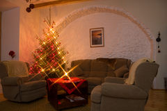 Living room. A photo of living room furnished with big and soft couch and armchairs and a decorated and shiney natural christmas tree / fir-tree in the left Stock Photos
