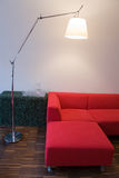 Living room. Interior with wooden floor, red sofa and lighting lamp Royalty Free Stock Photo
