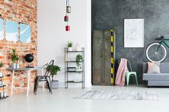 Spacious contrast color loft interior. Living room against concrete wall and workspace with plants against red brick wall in spacious contrast color loft Stock Photos