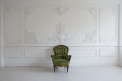 Living room with antique stylish green armchair on luxury white wall design bas-relief stucco mouldings roccoco elements Stock Photos