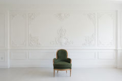 Living room with antique stylish green armchair on luxury white wall design bas-relief stucco mouldings roccoco elements Royalty Free Stock Images
