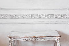 Living room with antique stylish light Coloured table on luxury white wall design bas-relief stucco mouldings roccoco Royalty Free Stock Photo