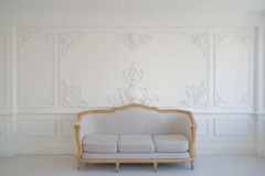Living room with antique stylish light sofa on luxury white wall design bas-relief stucco mouldings roccoco elements. Antique white sofa fretwork wall on Royalty Free Stock Photo