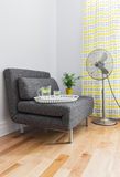 Living room with armchair and electric fan. Armchair and electric fan in a contemporary living room Royalty Free Stock Image