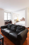 Living room, black leather sofa. Nice apartment, interior, black divan Stock Photo