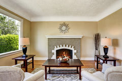 Living room with brick fireplace, deep brown furniture and rug. Stock Photography