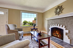Living room with brick fireplace, deep brown furniture and rug. Royalty Free Stock Photo