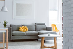 Living room with brick wall. Yellow decorative pillow on grey sofa in living room with brick white wall and simple coffee table royalty free stock photos
