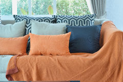 Living room with brown and orange tweed sofa. Modern living room design with brown and orange tweed sofa and black pillows Stock Photo