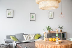 Living room with ceiling lamp. Living room with modern ceiling lamp and wooden accessories royalty free stock photography