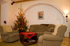 Living room and a christmas tree. Living room furnished with big and soft couch and armchairs and a decorated illuminated shiny natural christmas tree / fir-tree Royalty Free Stock Photo