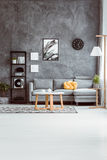 Living room with concrete wall. Spacious living room with coffee table on carpet in scandinavian style and grey sofa against concrete wall Royalty Free Stock Photos