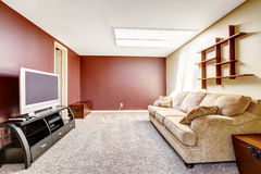 Living room with contrast color walls. Bright living room with contrast red wall, comfortable sofa and TV stock image