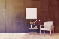 Living room, dark wood, poster toned. Living room interior with dark wooden walls, a white armchair, a coffee table and a framed square poster. 3d rendering mock Royalty Free Stock Photo