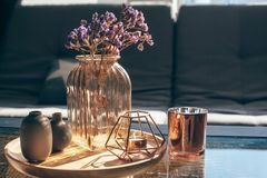Living room decor. Home interior decor in gray and brown colors: glass jar with dried flowers, vase and candle on the wooden tray on the coffee table over sofa Stock Photography