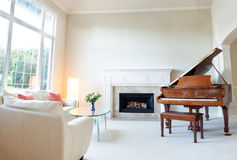Living room decorated with leather sofa and piano with burning f Stock Photography