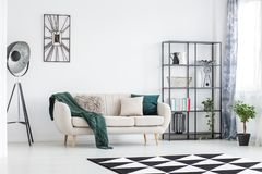 Living room design with decorations. Bright living room design with decorations on black metal rack and green blanket on cream couch royalty free stock images
