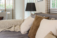 Living room design with pillows on grey sofa and black lamp Stock Image