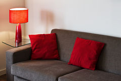 Living room detail. Detail of a modern livig room with sofa lamp and red cushions Royalty Free Stock Image
