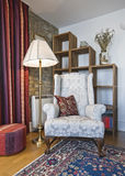 Living room detail. Detail of a living room with armchair and book shelves Royalty Free Stock Image