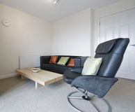 Living room detail. Modern living room detail with black leather sofa and armchair Stock Images