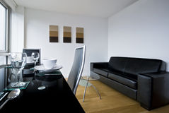 Living room with dining table. A living room, lounge with a black glass top table and diner set up Stock Photography
