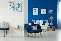 Living room with flowery patterns. Cozy blue and white living room with flowery patterns on pillows and posters stock photos