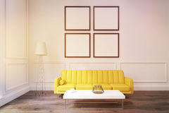 Living room with four posters, yellow sofa and a coffee table, t Stock Photos