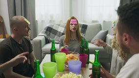 In the living room friends playing Who am I game with sticky papers on head stock video