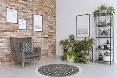 Grey Armchair Against Brick Wall Stock Image