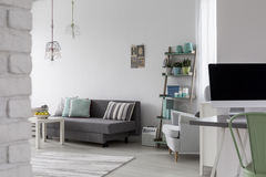 Living room with grey sofa, coffee table and white armchair. View from corridor on a living room with grey sofa, coffee table and white armchair Royalty Free Stock Photo