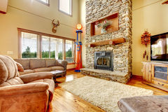 Living room with high ceiling, stone fireplace and leather sofa. Royalty Free Stock Images